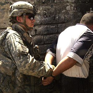 Arrest - A United States Army soldier arrests a man in June 2007, during the Iraq War