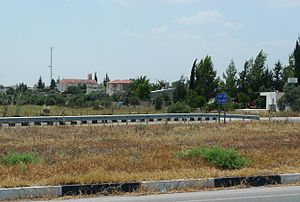 Angastina, Cyprus, 2012. Viewed from the northern Nicosia to Famagusta highway. Note the bell tower of Agia Paraskevi right of the communications tower