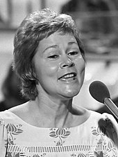 A black-and-white image of a woman with short hair singing into a microphone.