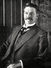 Photograph of a moustached middle-aged man in a dark suit and waistcoat, sitting in a chair while looking at the camera