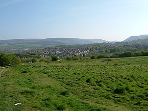 Across the overgrown site of the fort where no walls remain with the hills of Tintwistle and Peak Naze behind