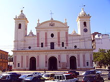Photo of a Spanish church with two towers, and three arched entrances. In front are parked cars.