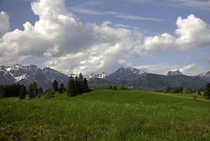 Molasse basin - The Bavarian Alps rise from the green hills of the Molasse basin. The hills consist of tilted molasse beds, erosional material transported from the mountains into their foreland.