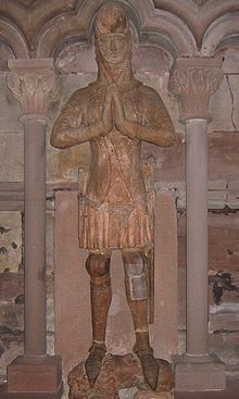 A grave effigy, standing, in armour, with hands together in prayer