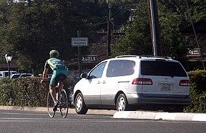 A bicyclist avoiding a minivan merging into tr...