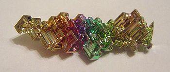 Masse cristallisée fortement colorée de bismuth oxydé en surface.