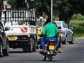 Boda boda biker and a passenger joining the main road.jpg