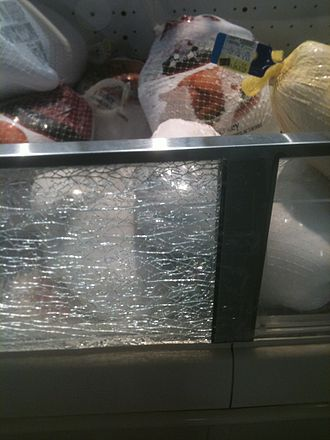 Tempered glass - Tempered safety glass, which has been laminated, often does not fall out of its frame when it breaks – usually due to the anti-splinter film applied on the glass, as seen in this grocery store meat case.