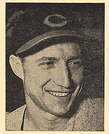 "A man wearing a dark baseball cap with a ""C"" on the center smiles and looks to the right."