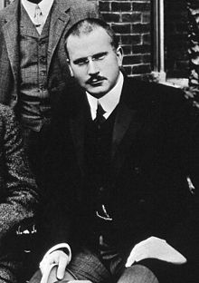 A black and white image of Carl Jung, wearing formal clothing.