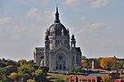 Über den Herbstbäumen steht eine hoch aufragende Kathedrale aus grauem Stein mit einem runden Kupferdach.