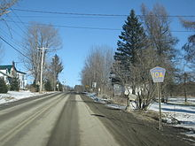 "Ground-level winter view of a two-lane road ascending a hill. A blue and yellow route marker reading ""Chenango County 10A"" is on the right side of the road in the foreground, and a house is on the left side in the background."