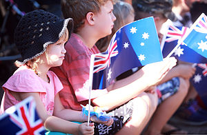 European Australians - Children wave Australian flags during an Anzac Day parade in Palmerston, Australia.