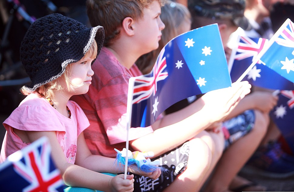 Children wave Australian flags during an Anzac Day parade in Palmerston, Australia, April 25, 2013, as U.S. Marines with the 1st Platoon, Lima Company, 3rd Battalion, 3rd Marine Regiment, Marine Rotational 130425-M-AL626-014