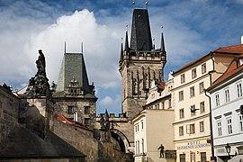 Deux tours de style gothique émergent de bâtiments anciens.