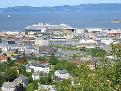 Cruise ship at port in Trondheim. Munkholmen and the stern part of Hurtigruten to the right. The body of water closest is Nidelva.