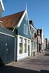 foto van Huis met zadeldak en houten topgevel op geprofileerde lijst boven een pui van baksteen