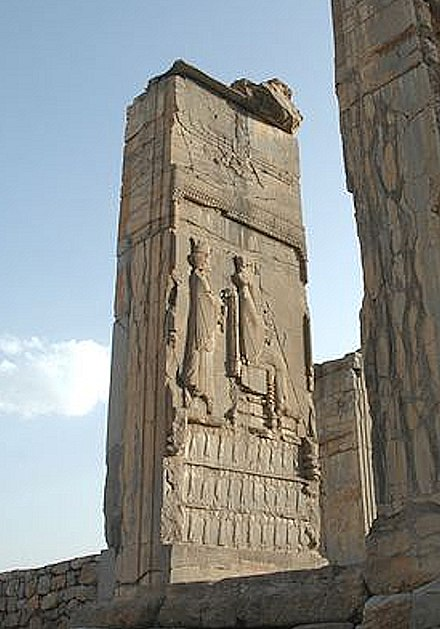 Xerxes being designated by Darius I. Tripylon, Persepolis. The ethnicities of the Empire are shown supporting the throne. Ahuramazda crowns the scene. Designation of Xerxes I.jpg