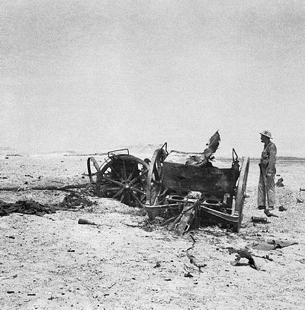 An RAF officer investigates wrecked artillery on the plateau above Habbaniya Destroyed iraqi artillery.jpg