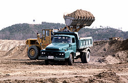 Earth moving equipment and dump trucks move dirt.JPEG
