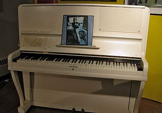 "The 1910 piano on which John composed his first five albums, including his first hit single, ""Your Song"" EltonJohnPiano.jpg"