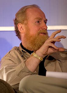 Action portrait of a man in his fifties with a bushy, strawberry-blond beard seated while speaking wearing a safari jacket and gold watch