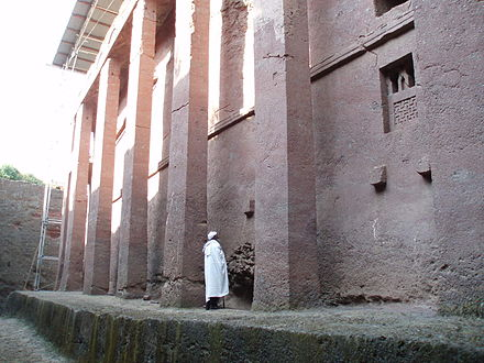 Man standing beside the walls of Bete Medhane Alem, believed to be the largest monolithic church in the world. - Lalibela