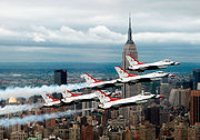 Six F-16 Fighting Falcons of the U.S. Air Force Thunderbirds aerobatics team fly in delta formation in front of the Empire State Building in Manhattan during a photoshoot preceding the 2005 Jones Beach airshow.