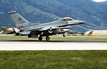 En jagerfly med AV merket på halen tar av fra en rullebane.
