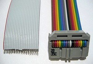 Ribbon cable - Left: 20-way grey ribbon cable with wire no. 1 marked red, insulation partly stripped. Right: 16-way rainbow ribbon with IDC connector.