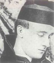 Monochrome head-and-shoulders photo of Fr. Rolfe in coat, with biretta