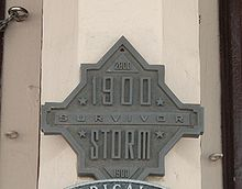 "A building with a plaque reading ""1900 Storm Survivor"", with the year 2000 at the top and 1900 again at the bottom"