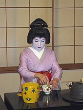 A geisha wearing a pink kimono sat at a black table, whisking a small cup of tea