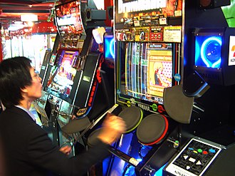 Arcade game - A man playing a drumming arcade game (Drummania) in Tsukuba, Ibaraki, 2005.