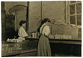 Two women packing glass in factory