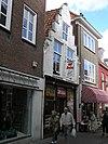 foto van Huis met geverfde trapgevel. Geprofileerde dekplaten en segmentvormig fronton. Staafankers. Winkelpui