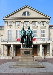 "Photograph of a large bronze statue of two men standing side by side and facing forward. The statue is on a stone pedestal, which has a plaque that reads ""Dem Dichterpaar/Goethe und Schiller/das Vaterland"". Behind the monument there is a large, 3-storey building with an elaborate stone façade."