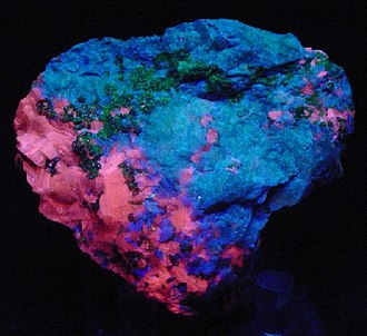 Hardystonite - Hardystonite is fluorescing blue in this Franklin Furnace specimen. Red is calcite, and green is willemite (size: 7.0 x 6.0 x 3.2 cm)