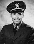 Black-and-white photo of Henry Fonda—a white man in his 40s, wearing Navy uniform, has dark eyes and hair and is smiling.