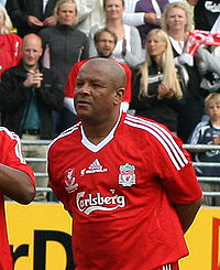 A black man standing with a red shirt. The shirt has emblems in white and the words Carlsberg in the middle.