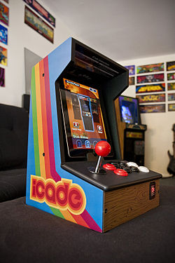 An Apple iPad rests within a portable wooden arcade cabinet decorated in a bright, retro style.