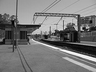 Railway electrification in Australia - The Indooroopilly railway station before the refurbishment with the power lines which can be seen over the rail line.