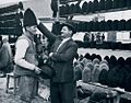 Iosif Berman - Un ţăran işi inlocuieste pălăria cu o cuşmă de oaie, la taraba unui comerciant.jpg