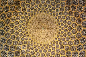 The interior of the dome which is inset with a network of lemon-shaped compartments, which increase in size as they descend from a formalised peacock at the pattern inlaid on plain stucco