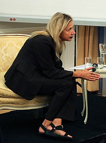 Talking at embassy leaning forward in yellow chair
