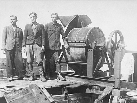 A Sonderkommando 1005 unit stand next to a bone crushing machine at the Janowska concentration camp Jewish prisoners forced to work for a Sonderkommando 1005 unit pose next to a bone crushing machine in the Janowska concentration camp.jpg