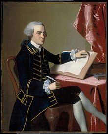 Full-length portrait of a young man seated at a table. He wears a finely tailored dark suit, knee breeches with white stockings, and a wig in the style of an English gentleman. He holds a quill pen in his right hand, and is turning the pages of a large book with the other hand.