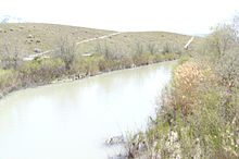 A river with plants on either side. A hill rises on the right side.