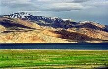 pâturage vert au premier plan, un plan d'eau au milieu des sol, et les montagnes en arrière-plan. L'ombre des nuages sont visibles sur les montagnes, tandis que les plus hauts sommets les plus éloignés ont une dispersion de la neige