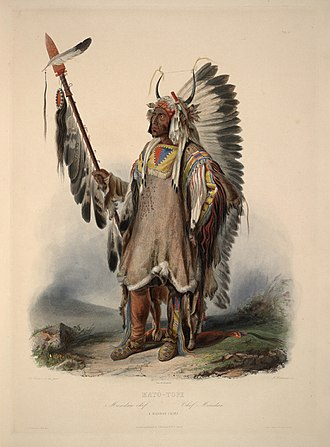 """Mato-tope - Mato-tope holding a lance and wearing painted and quilled shirt: aquatint by Karl Bodmer from the book """"Maximilian, Prince of Wied's Travels in the Interior of North America, during the years 1832–1834"""". The shirt is made of """"bighorn leather""""."""